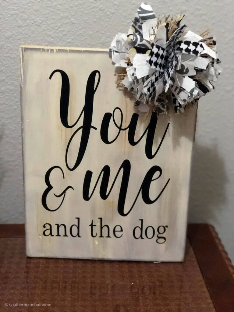 """messy bow on top of a sign that says """"you and me and the dog"""""""