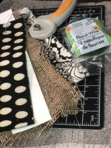 Supplies for a DIY messy bow - rotary cutter, fabric, burlap, and floral wire