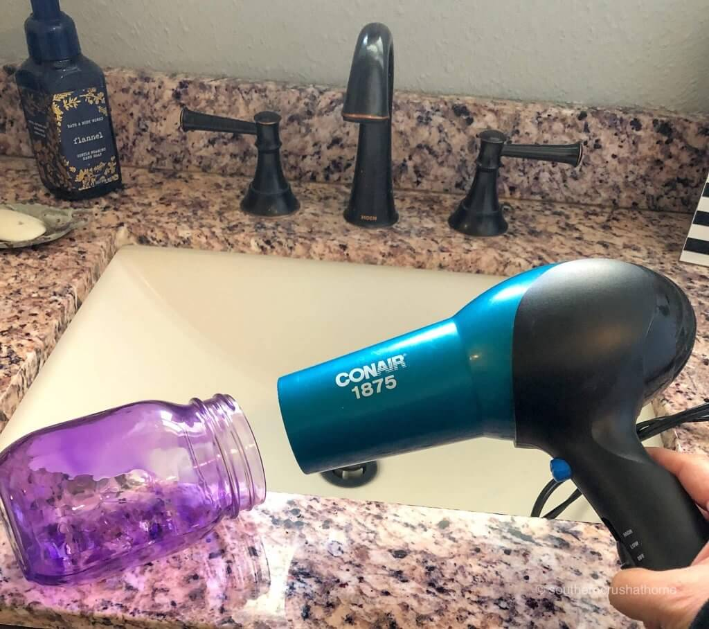Using a hair dryer to dry the inside of a purple-stained mason jar