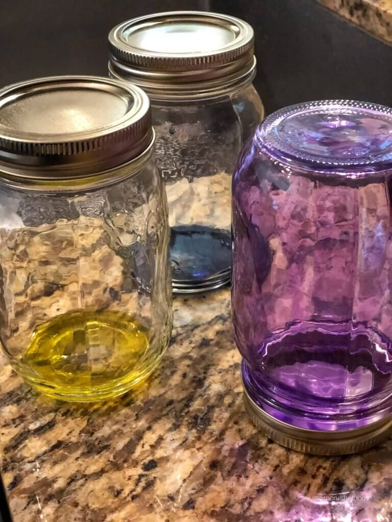 A purple mason jar is upside-down as glass stain coats the sides