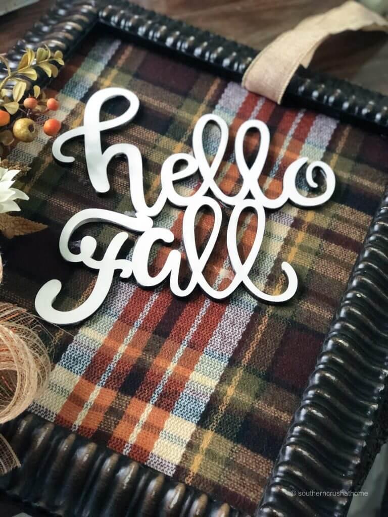 Hot gluing hello fall cutout to plaid fabric