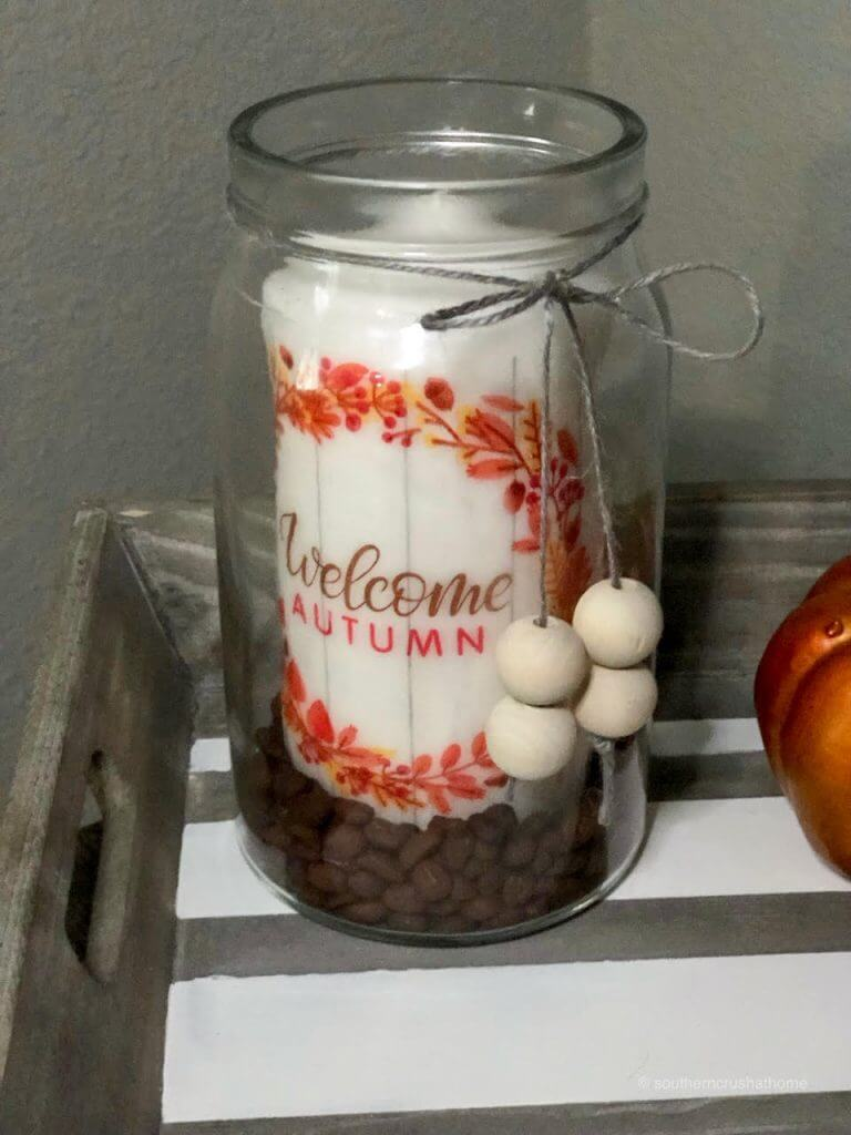 Decorated jar for fall with coffee beans and a candle