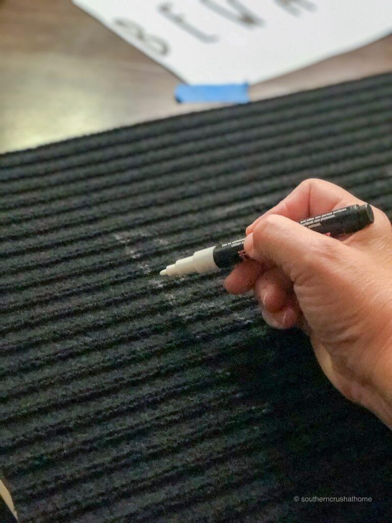 Using a chalk pen on a Halloween Doormat