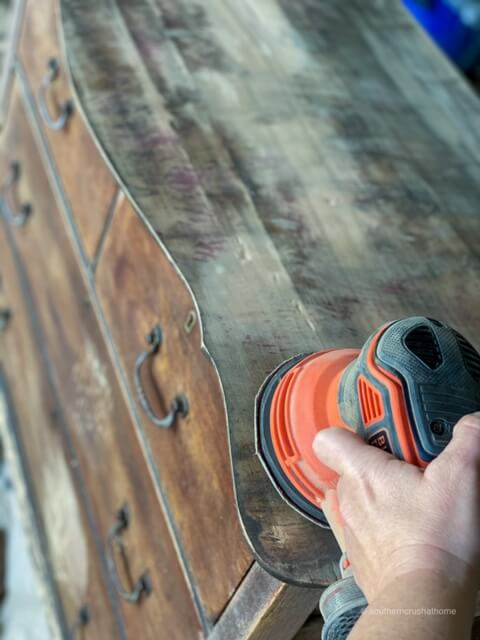 Using a sander to sand the top of an old dresser