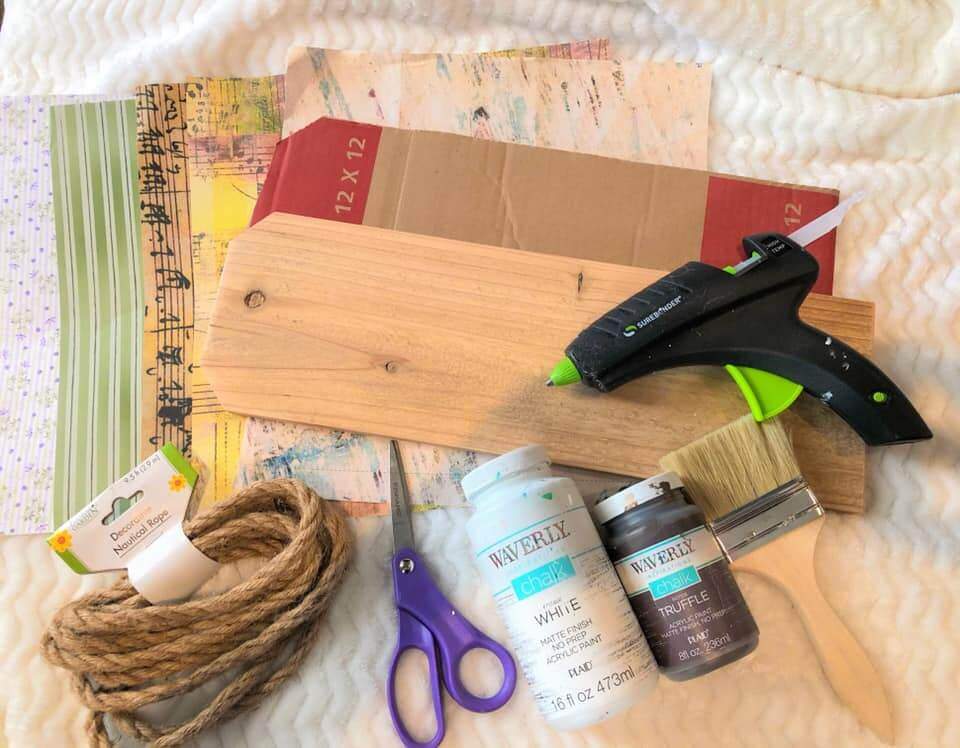 Supplies needed for a diy floral banner including wood, rope, glue gun, paint, scrapbook paper