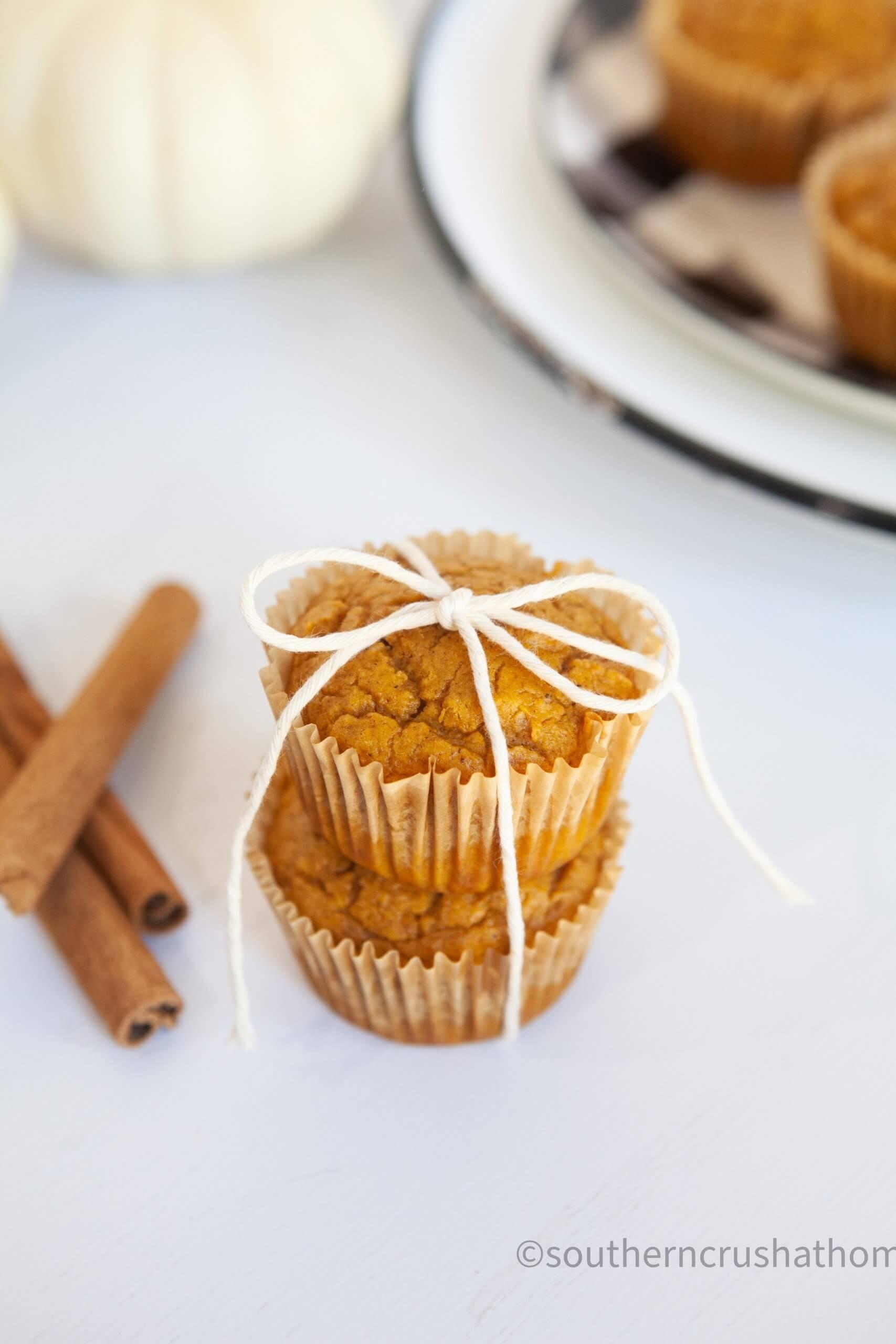 3 ingredient pumpkin muffins stacked with cinnamon sticks