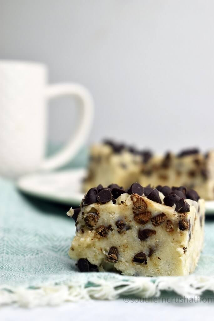 Cookie dough fudge with a white mug in the background.