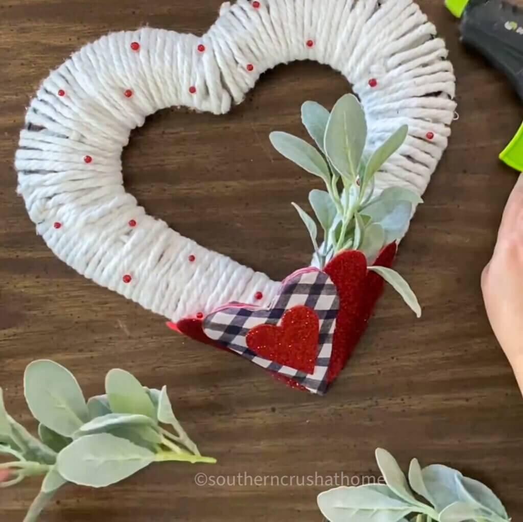 adding greenery to heart pocket of diy wreath