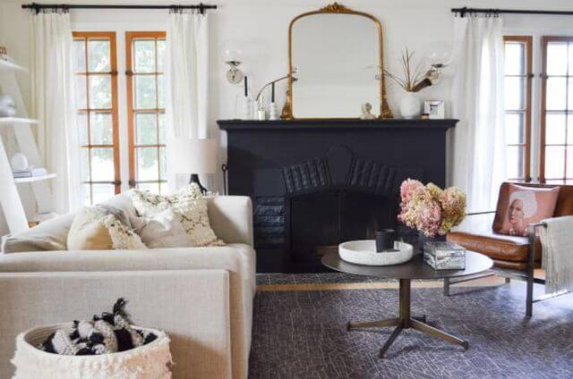 living room with black fireplace and gold mirror