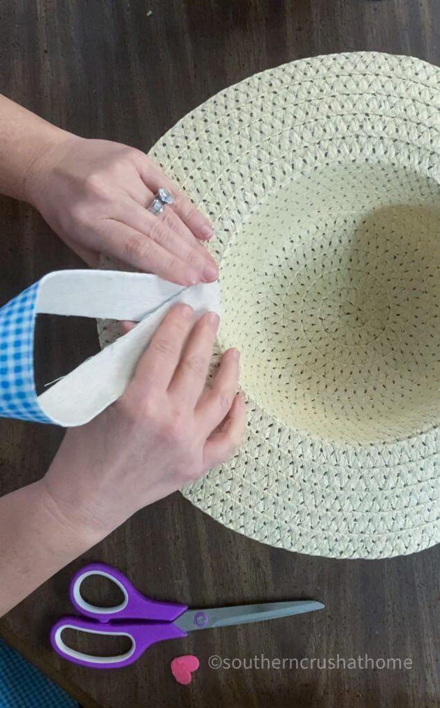 adding ribbon on sun hat for hanging