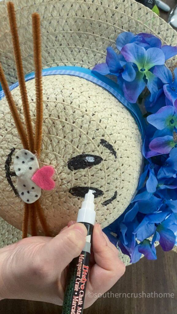adding white paint to the bunny eyes on sun hat