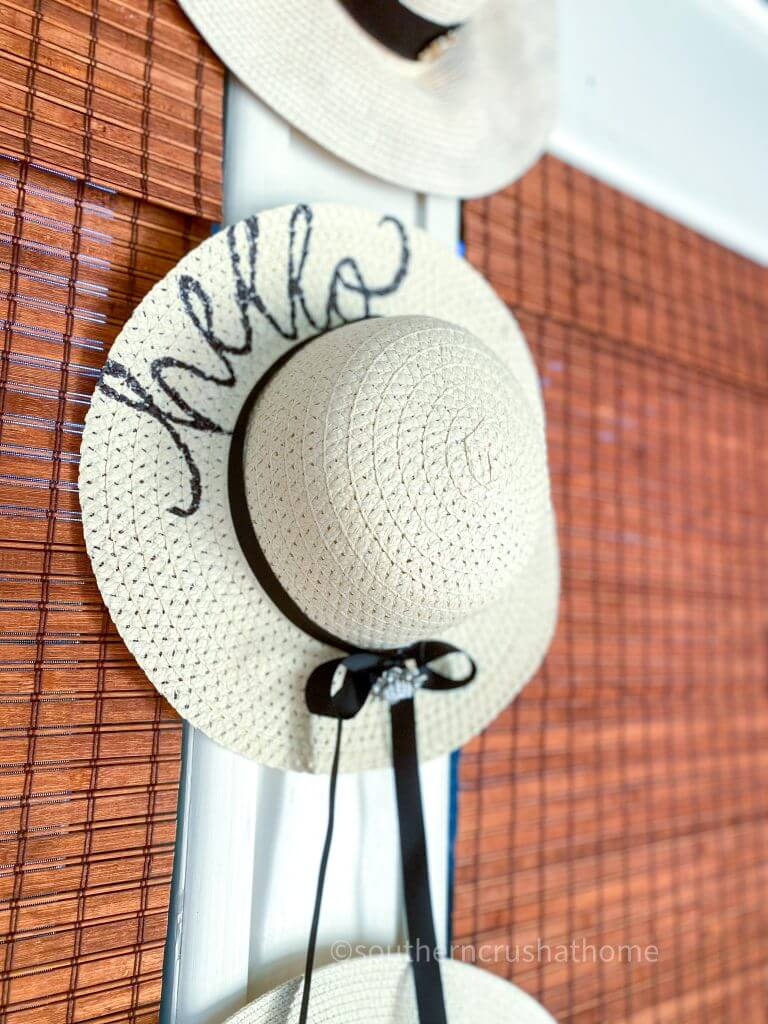 trio of sun hats hanging on porch wall