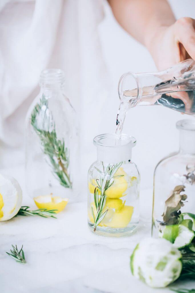 DIy infused vinegar on table with white backdrop