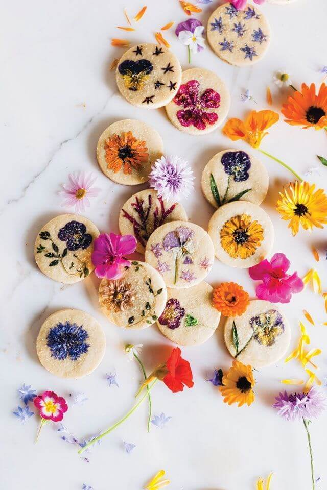 cookies with edible flowers on marble counter