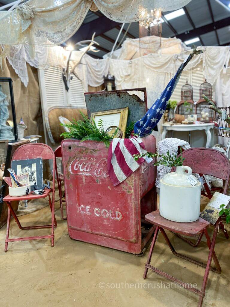 vintage coca cola cooler with red metal chairs and american flag