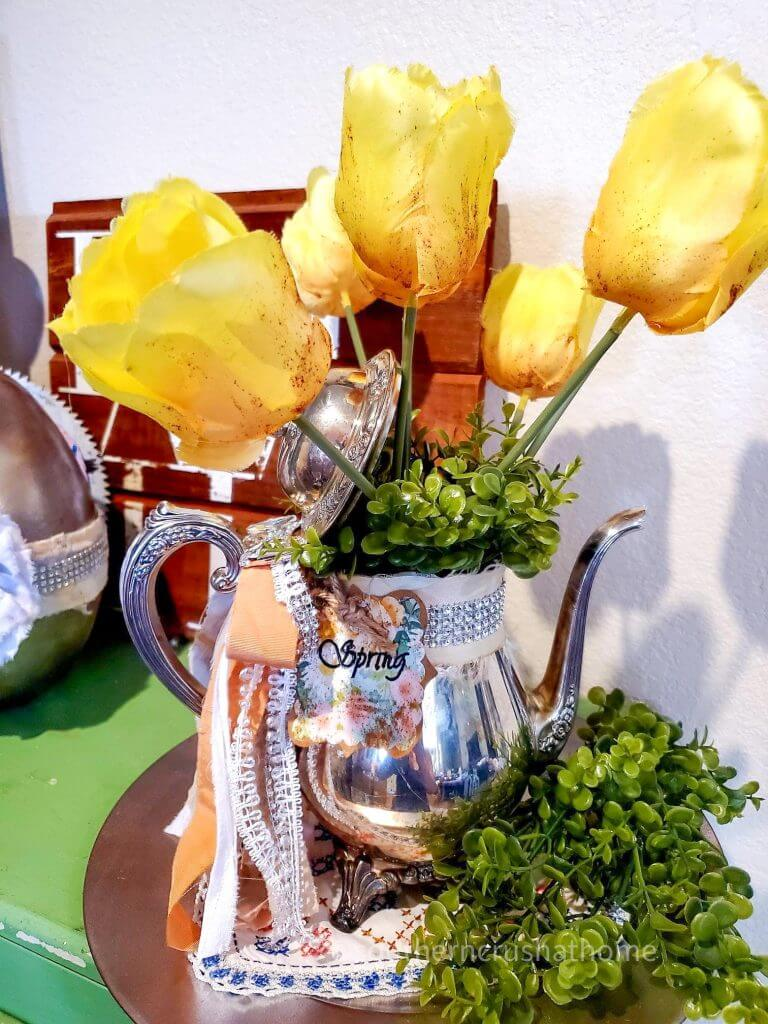 tea pot centerpiece on table with yellow roses