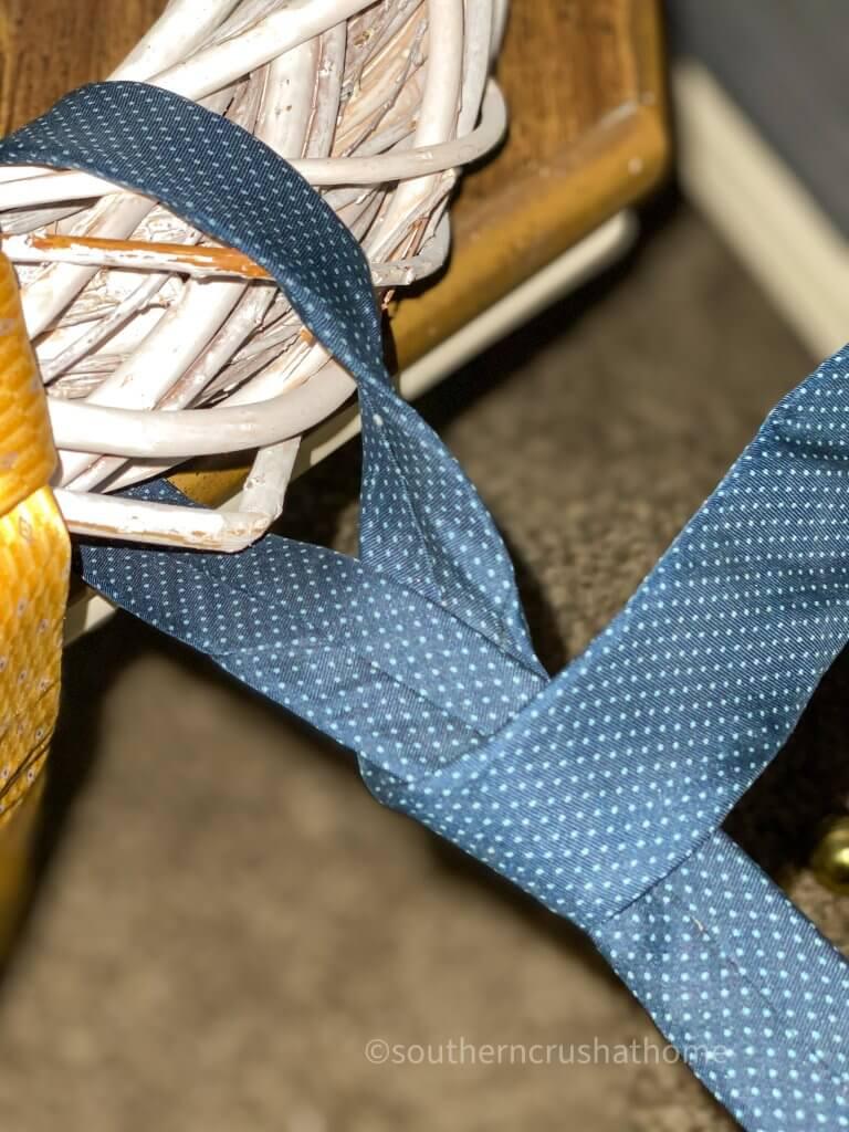 close up of necktie being wrapped around wreath