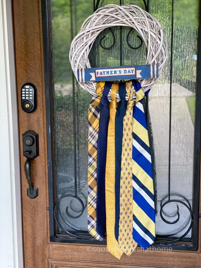 finished necktie wreath hanging on front door