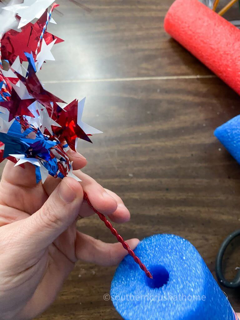 placing Fourth of July picks into pool noodle