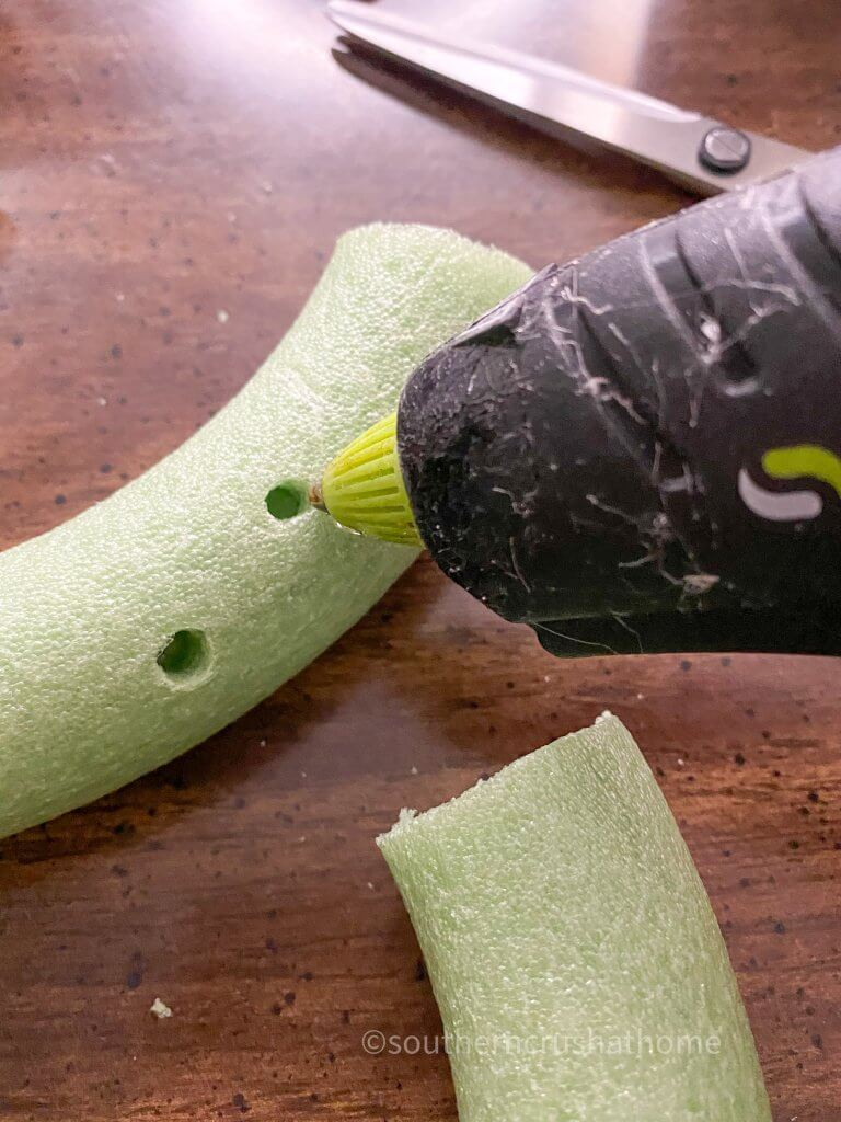 adding hot glue into holes for succulents