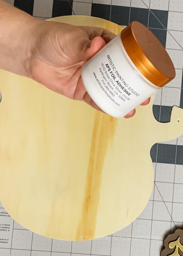 adding foil adhesive to wood pumpkin