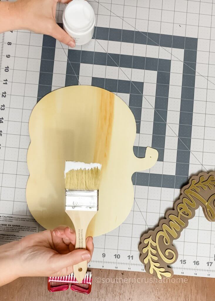 using chip brush to add adhesive to pumpkin