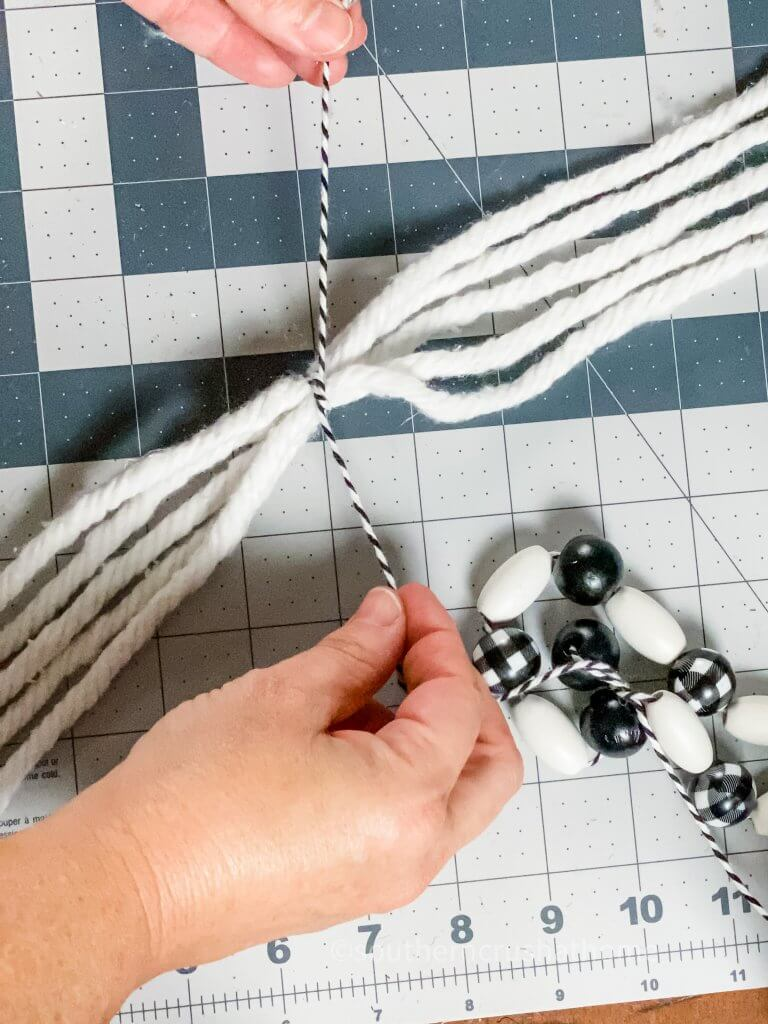 tying black and white bakers twine around mop head strands